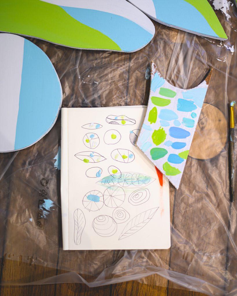 Sculpture en bois peint à l'acrylique vert et bleu réalisée par Cécile Jaillard. Work in progress et test de gammes de couleurs sur carnet d'esquisses