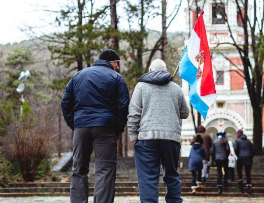 Homme portant un drapeau Bulgare devant le monastère pendant la fête commémorative de la bataille de Chipka en Bulgarie.